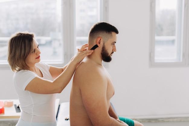 Терапевт приклеивает кинезиологическую ленту на шею пациента.
