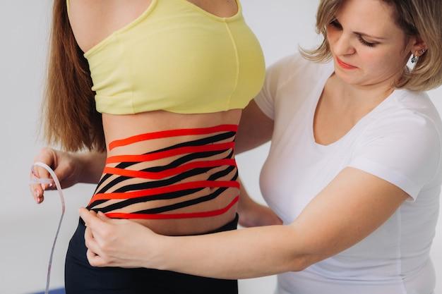 女性の腹にキネシオテープ。彼女の腹に運動学弾性治療テープを持つ若い白人女性。