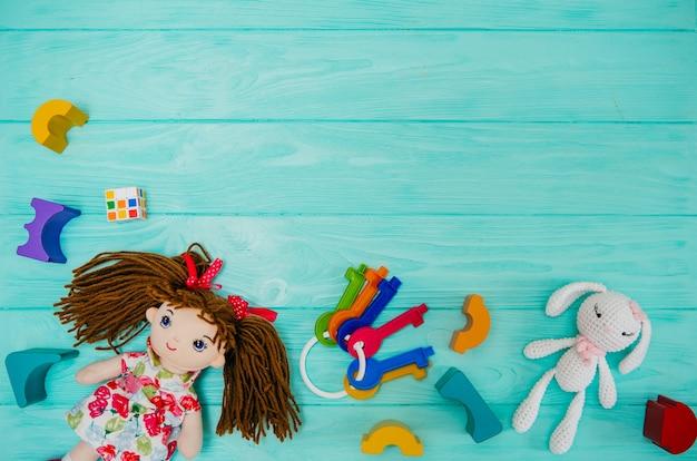 青い背景に木製のビルディングブロックを持つ子供の人形