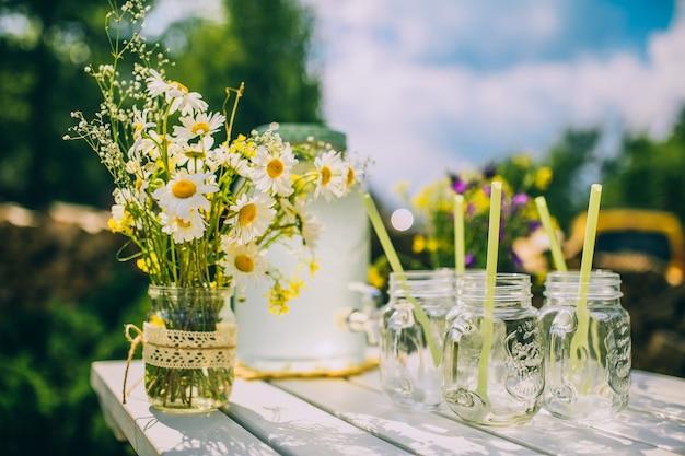 屋外で木製のスタンドでタップを持つガラス瓶のレモネード
