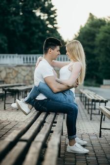 Молодая влюбленная пара позирует на скамейке в парке