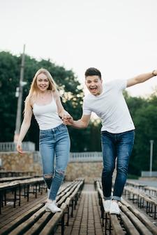 笑いと公園のベンチに手を繋いでいる愛の若いカップル