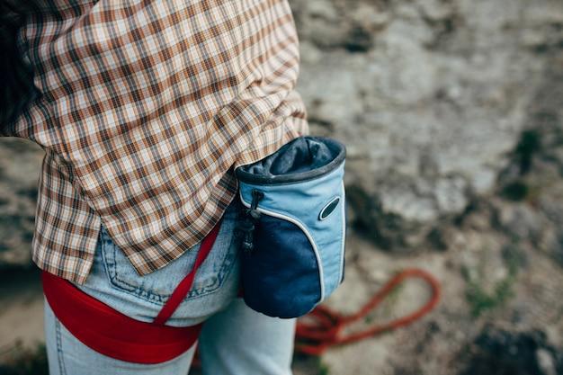 男性ロック・クライマーは崖を登る準備をします