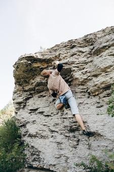 勇敢な若い男が崖を登る
