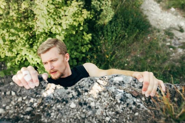 勇敢な若い男が崖の上に登る