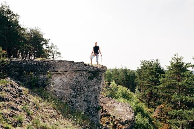 ロープで崖の端に立っているロック・クライマー