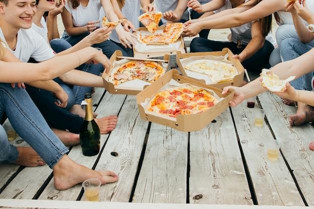 木製の桟橋でピザを食べている友人