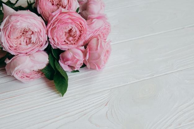 白いテーブル、夏のコンセプトにピンクのバラ