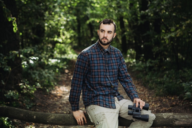 双眼鏡で枝の上に座ってひげを生やした男