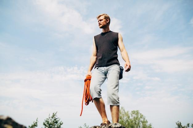 ロープを使って岩の上に立っている男性ロック・クライマー