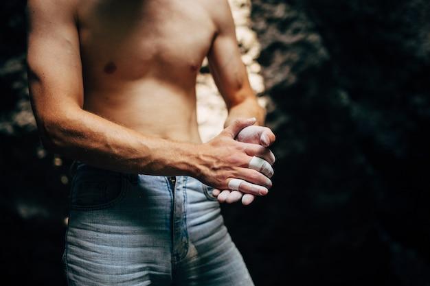 登山の前に彼の手に粉末チョークマグネシウムを適用するロック・クライマー