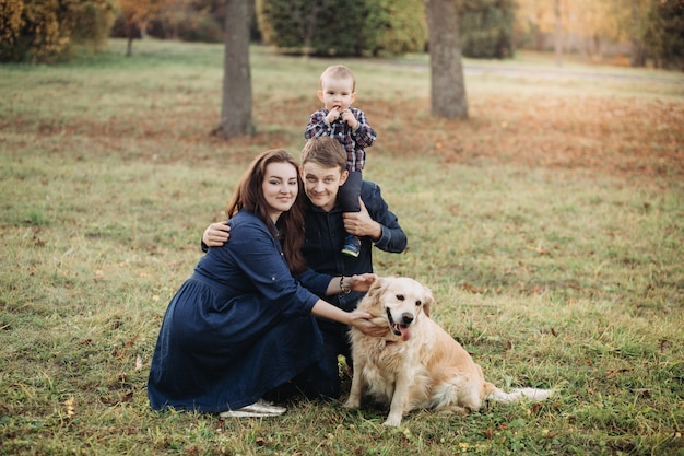 秋の公園で子供とゴールデン・リトリーバーと家族