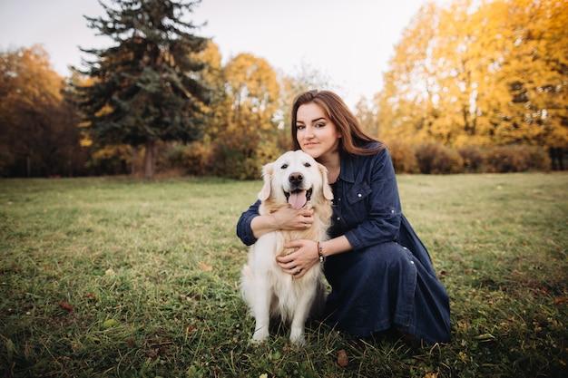 美しい秋の公園でゴールデンレトリーバーを持つ若い女性
