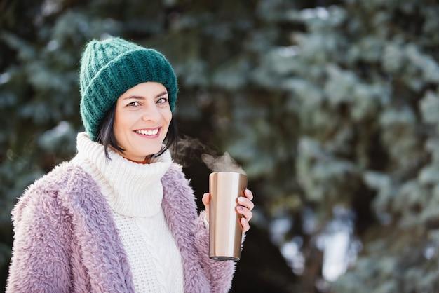 ホットコーヒーと旅行ステンレス鋼マグカップを保持している冬の日に歩く若い女性。再利用可能なウォーターボトル。