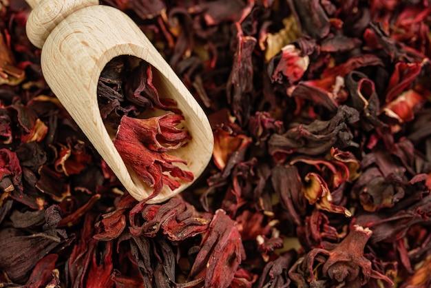 ハイビスカスティー。閉じる。上面図。風邪やインフルエンザのためのビタミンティー。木のスプーンでお茶の花びら。