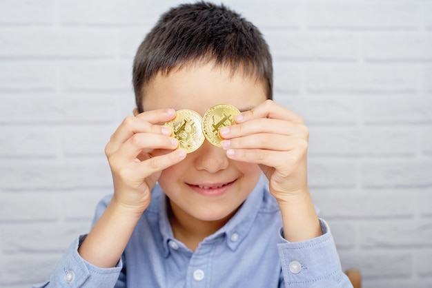 Маленький мальчик, держа биткойн монеты. монета фокус. ребенок держит криптовалюту в металле. технология майнинга или блокчейна.