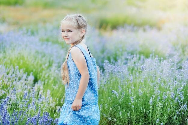Маленькая девочка в сиреневом поле. детская фантазия. усмехаясь цветки обнюхивать девушки в поле лаванды лета фиолетовом.