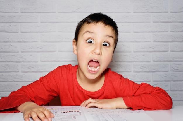 Расстроенный скучный школьник делает домашнее задание. образование, школа, концепция трудности в обучении.