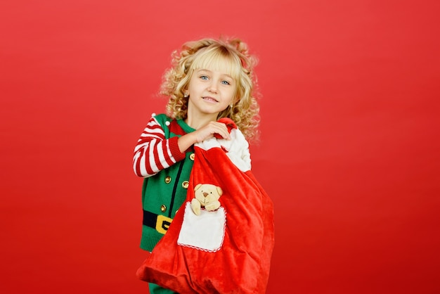 明るい赤の鮮やかな色の背景にサンタエルフヘルパー衣装の少女。