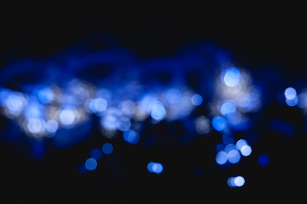 キラキラサークルと輝く抽象的なボケ背景の青い色
