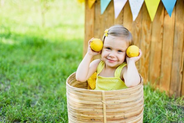 Девушка маленького ребенка с лимонами на стойке лимонада в парке. портрет забавного ребенка в корзине с фруктами