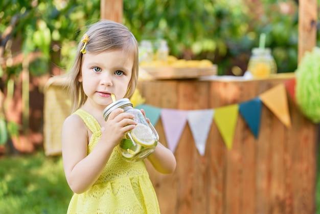 夏のさわやかな天然ドリンクレモネード。少女は公園のレモネードスタンドで自然なレモネードを飲みます。