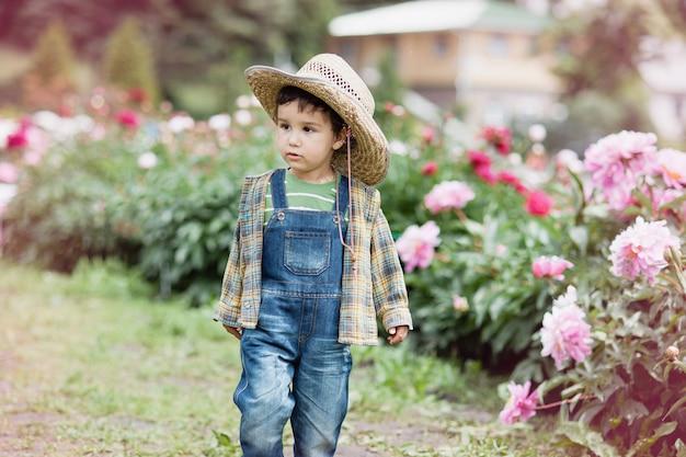 ピンクの牡丹の近くの小さな農家の少年