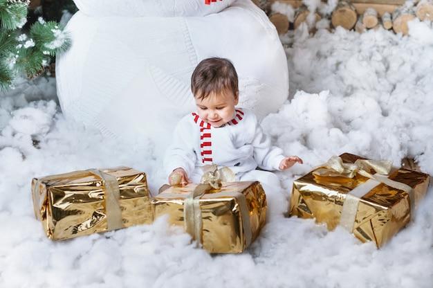 大きな雪だるまによって家の内部に座っているとサンタを待っている雪だるまの衣装の少年