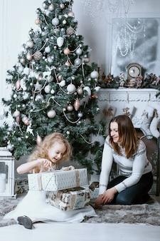Мать и дочь открывают подарки под елкой