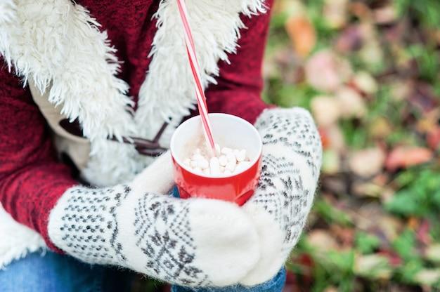 温かい飲み物のカップを保持していると草の上に座っている女の子の手