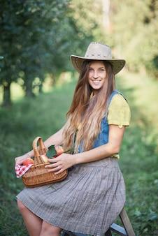 リンゴ園でアップルを持つ少女果樹園でオーガニックアップルを食べる美少女