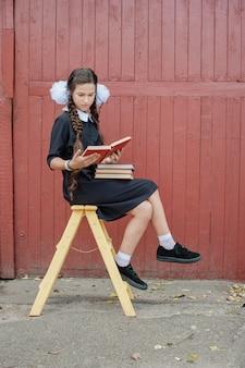 黄色の階段の上に座って本を持つ女子高生
