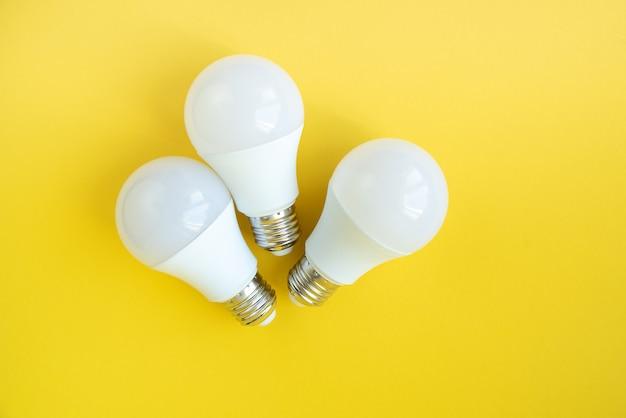 Три светодиодные лампочки на желтом фоне. концепция энергосбережения.