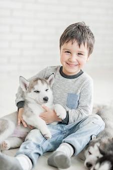 眠っている小さな男の子とハスキーの子犬