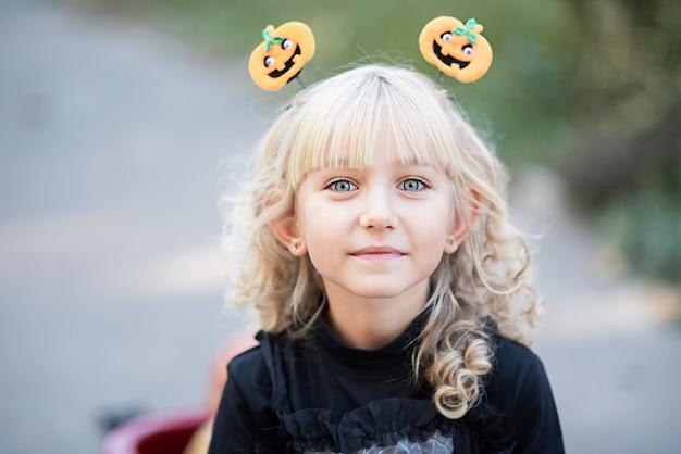 魔女の衣装の少女は、屋外のハロウィーンを祝うし、楽しい時を過します。