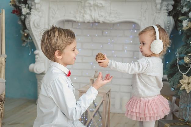Брат и младшая сестра под елкой. улыбающийся мальчик, давая рождественский подарок девушке. семейный отдых