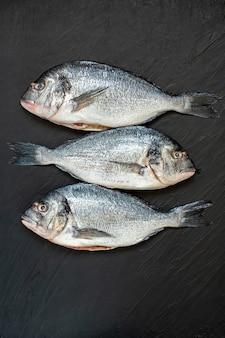 Сырая рыба хек. пять сырых филе рыбы с органическими свежими помидорами на льду на темном