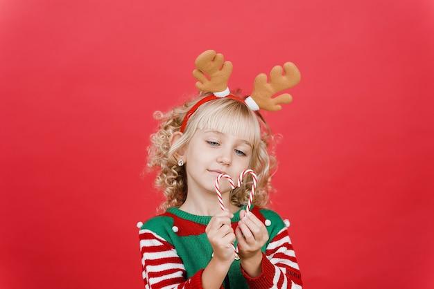 Маленькая девочка в костюме помощник эльф санта на фоне ярко красный яркий цвет.