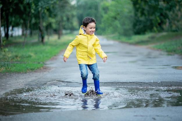 Мокрый ребенок прыгает в луже.
