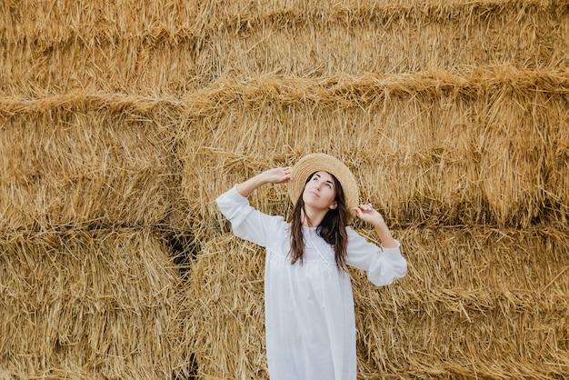 若い女の子は、フィールドで干し草ベール近く夏の白いドレスを着ています。