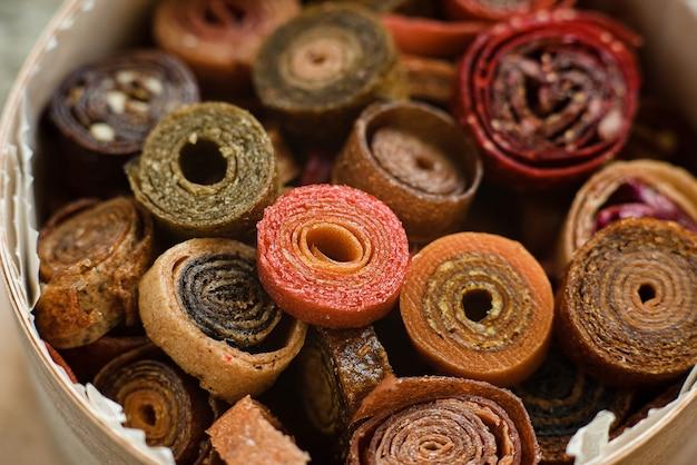 Сладкое пюре из фруктовой пастилки. фруктовые рулетики домашнего приготовления. натуральные сладости из сушеных ягод и фруктов.