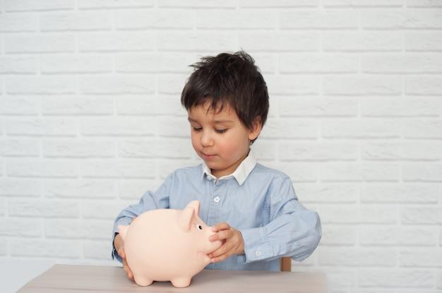 Мальчик с копилкой свиньи. детство, деньги, инвестиции и концепция счастливых людей