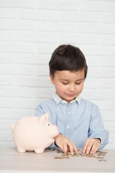 豚の貯金箱を持つ少年。幼年期、お金、投資、幸せな人々の概念