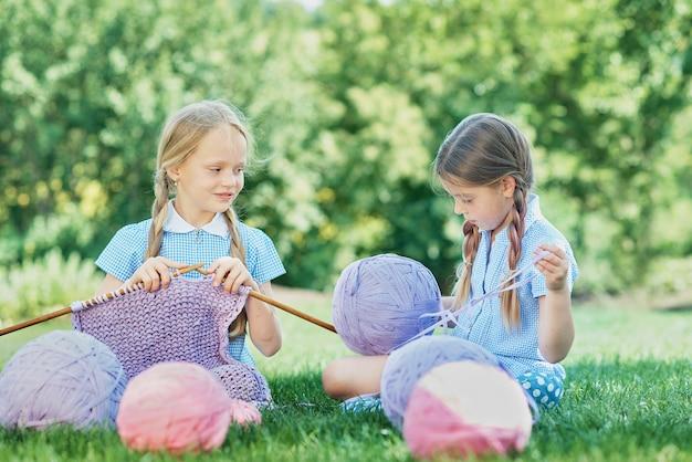Ребенок сидит на зеленой траве и вязание свитер с иглами на летний день.