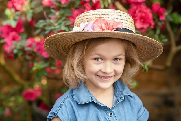 フラワーバスケットを持つ幼児。ピンクの花を保持している女の子