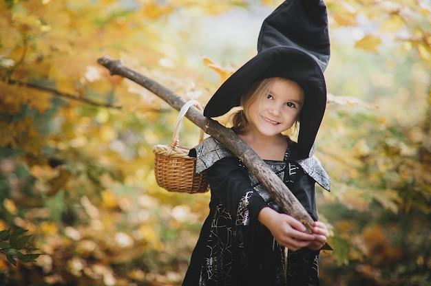 Красивая девушка ведьма. маленькая девочка, в которой костюм празднуют хеллоуин на улице и развлекается. детский трюк или лечение