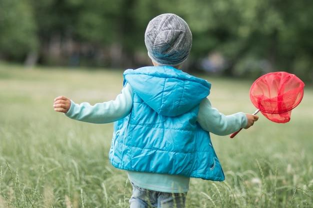 Мальчик с сеткой-бабочкой бабочка ловит