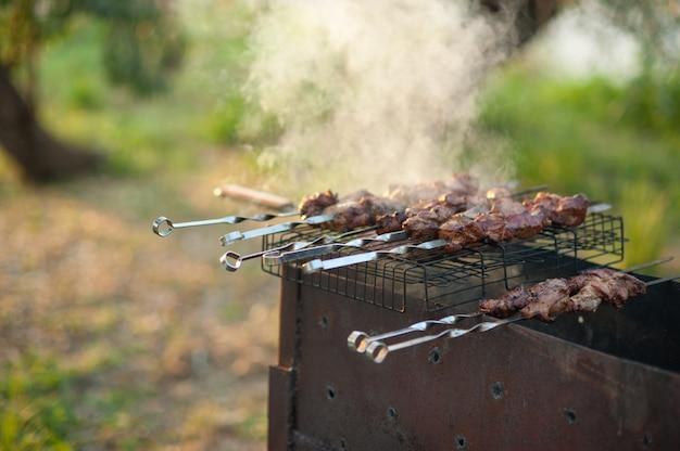 グリルでシシカバブ。炭火でバーベキューグリルで準備するシャシリクのマリネ。