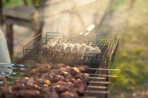 Шашлык на гриле. маринованный шашлык готовится на гриле на углях.