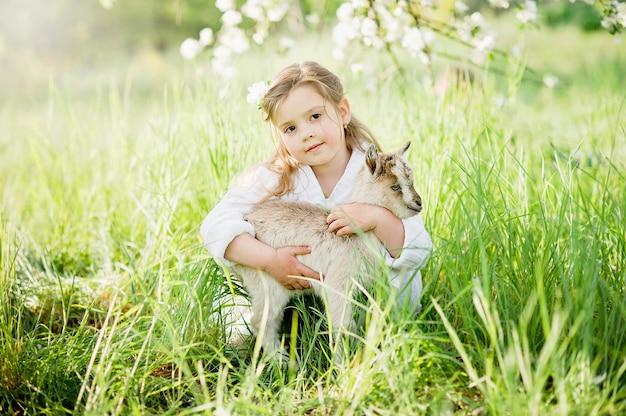 赤ちゃんヤギを持つ少女。子供と動物の友情。幸せな子供時代。